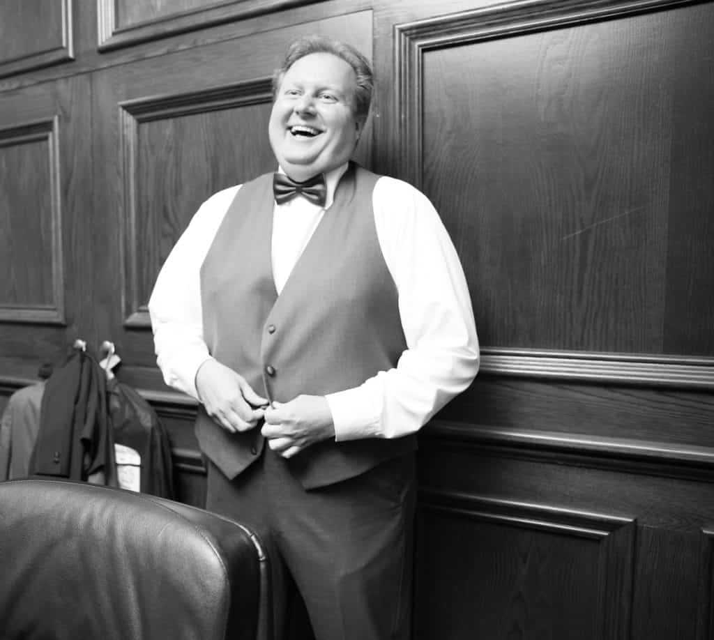 Groom laughing as he prepares for his wedding