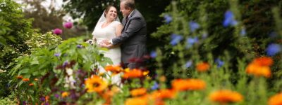 bride and groom looking at each other in park with flowers