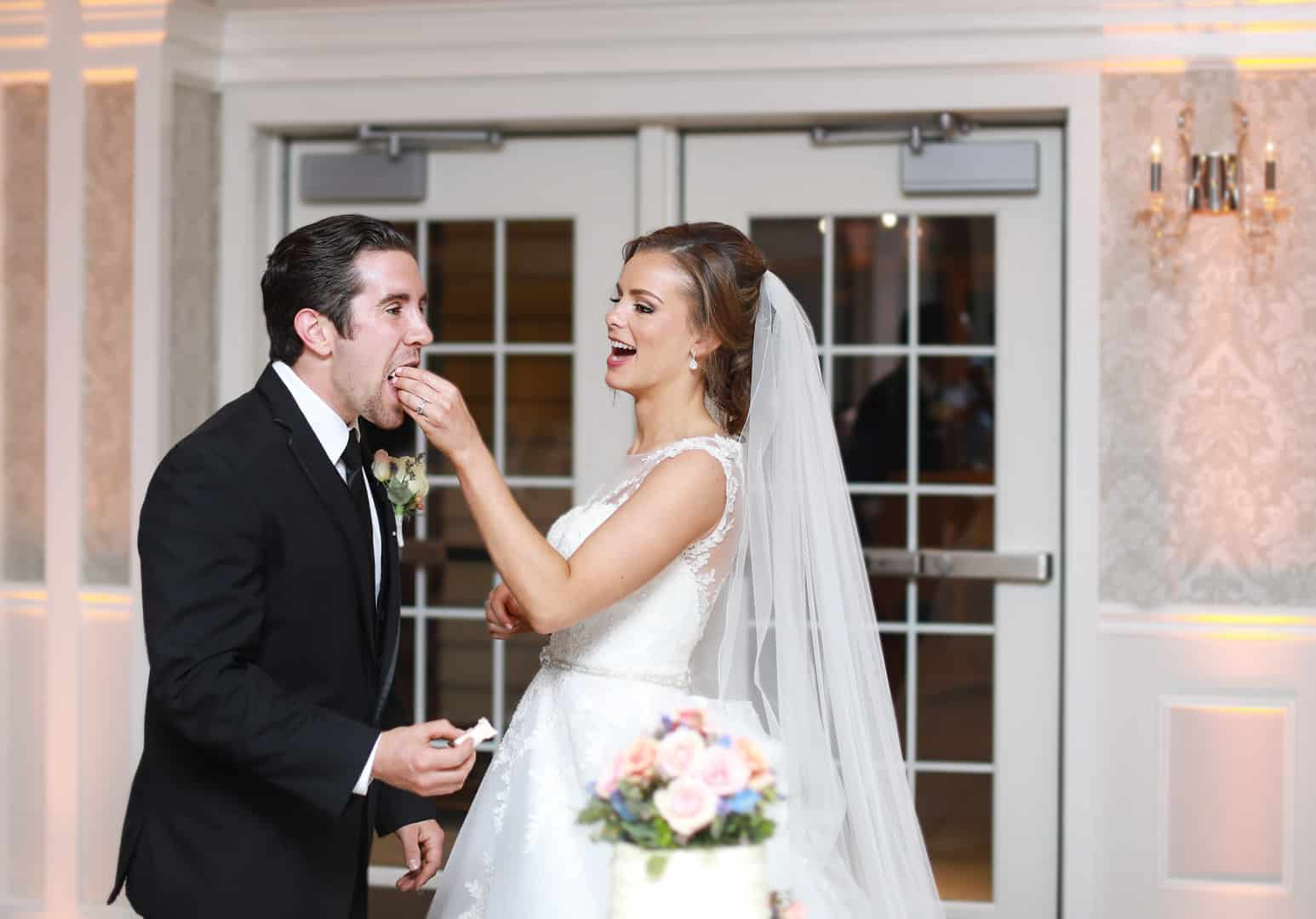 bride feeding the groom cake at reception