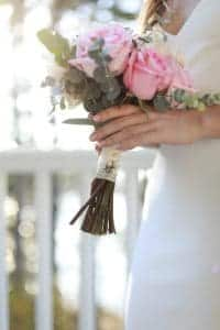 Bride holding her bouquet on the porch of her wedding