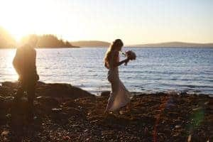 bride and groom walking on the beach, sunset, blue ocean