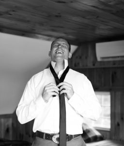 Groom tying his tie in black and white