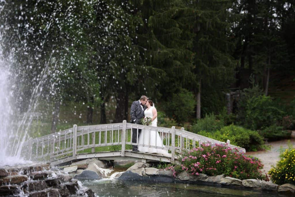 bride and groom on a bridge over water, water fountain in front, green trees in the back