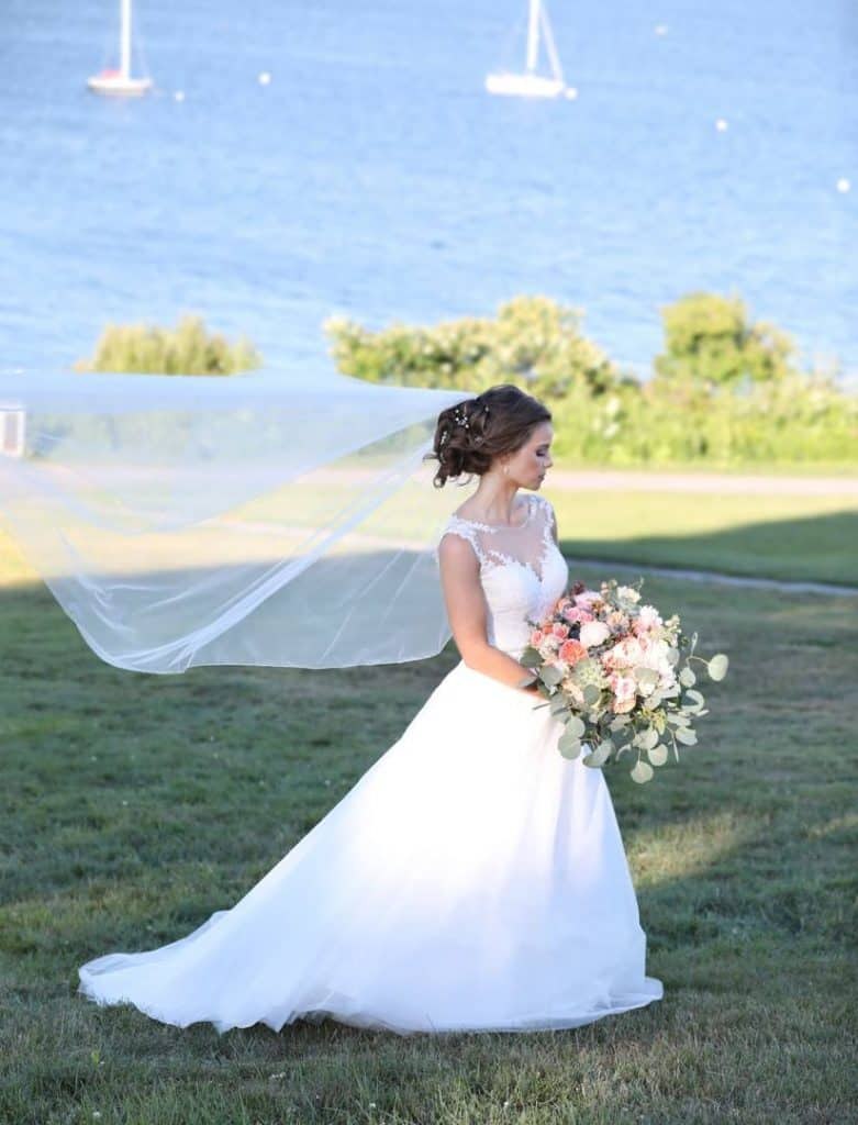 bride facing away from the camera holding bouquet near the ocean, boats in the background