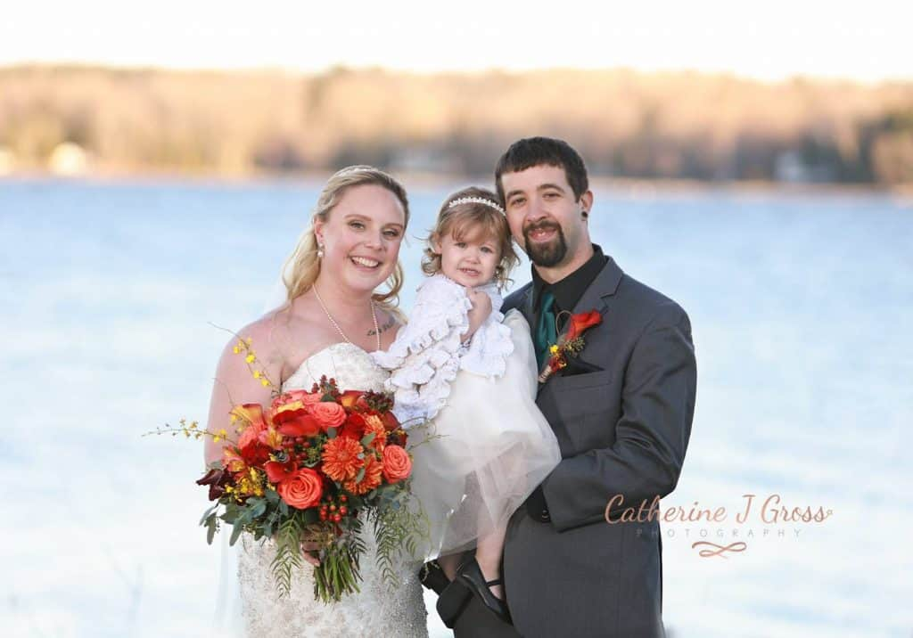 bride and groom with child looking at the camera, lake in background, red and orange flowers